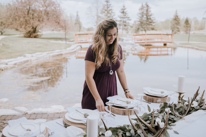 Wedding planner setting up rustic table design