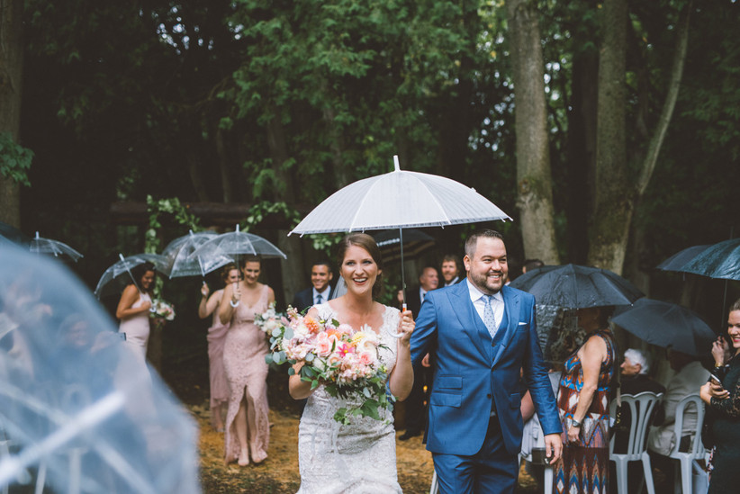 Bride and wedding party holding umbrellas an ceremony