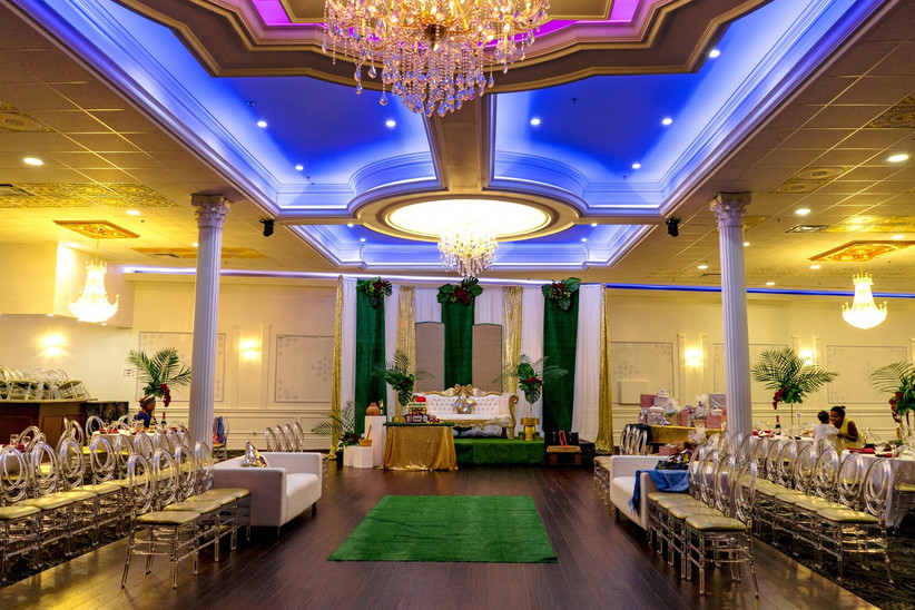 Wedding venue set up with lighting and ghost chairs