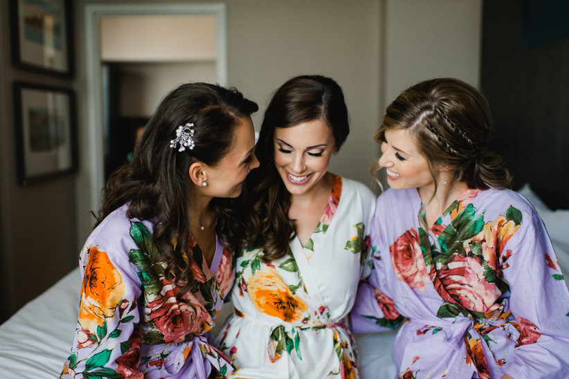 Bride and bridesmaid getting ready wearing floral robes