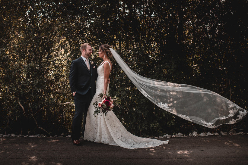Wedding porrait with bordered bridal veil blowing in the wind