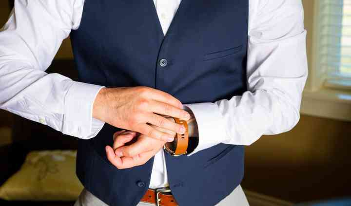 Groom putting on suit & watch