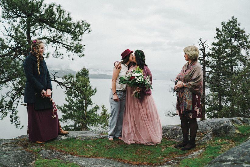 Brides kissing at gay wedding ceremony