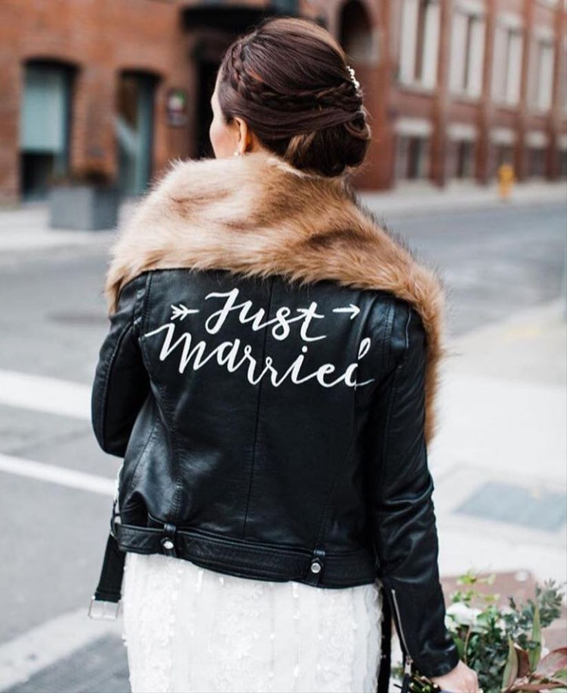 "Bride wearing leather jacket with ""Just Married"" scripted on the back and a fur stole"