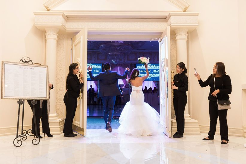 Bride and groom entrance before a wedding slideshow