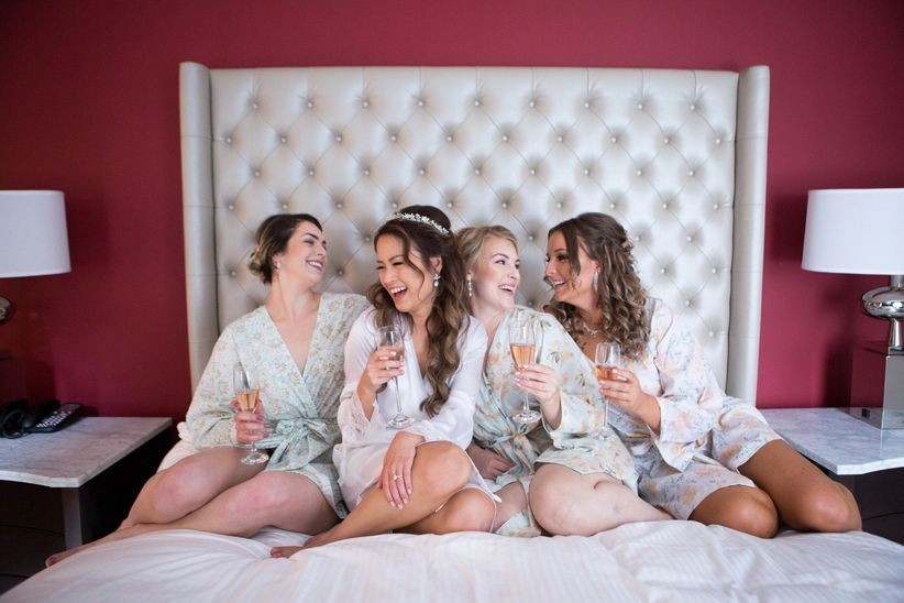Bride and bridesmaids in matching robes sipping champagne