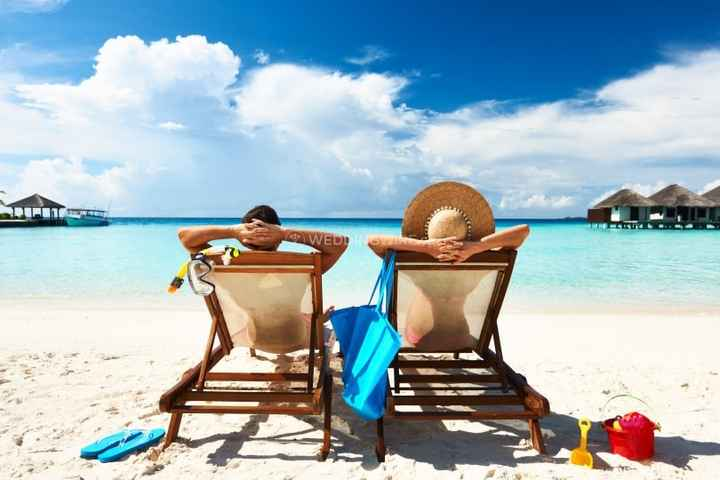 Couple lounging in beach chairs on honeymoon
