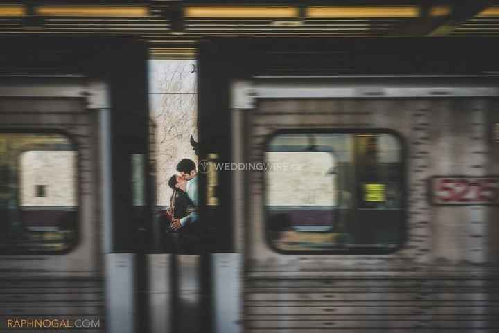 couple kissing in a train station, shot between train carts