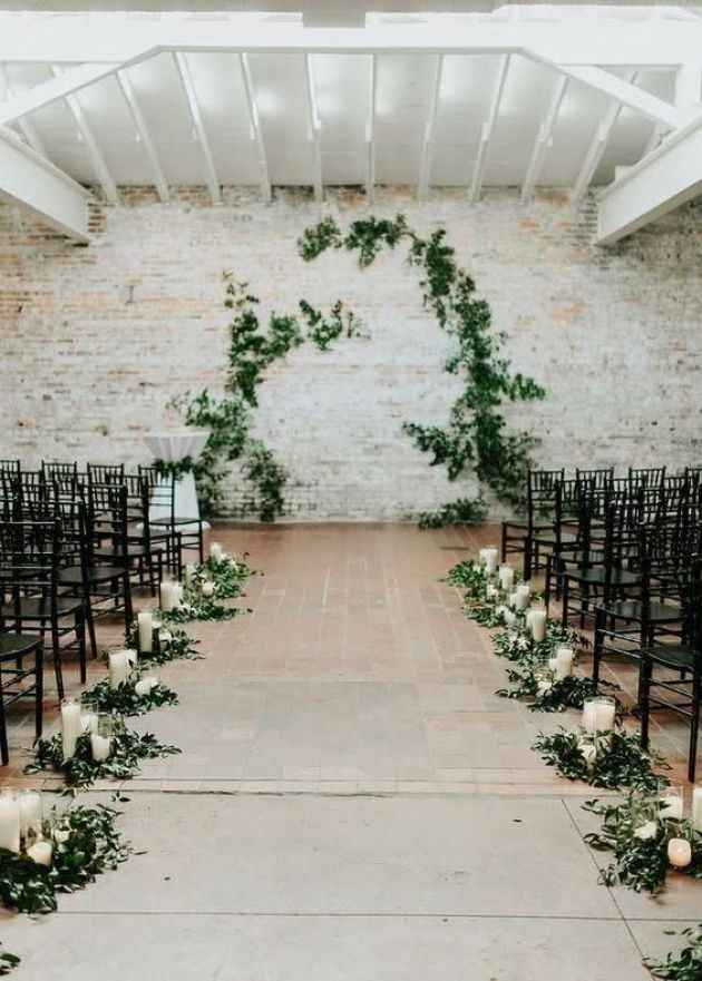 black chiavari chairs at a wedding ceremony, greenery arch