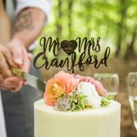couple cutting a wedding cake, pink white and green flowers