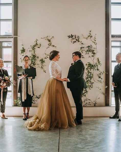 same sex wedding ceremony with floral backdrop